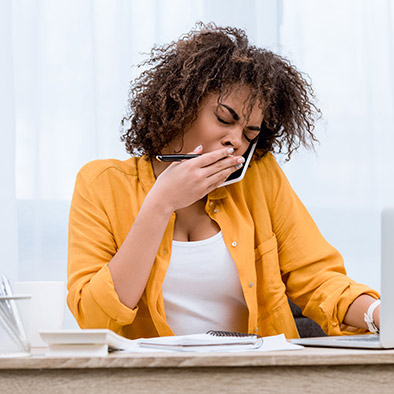 A woman is yawning, looking tired
